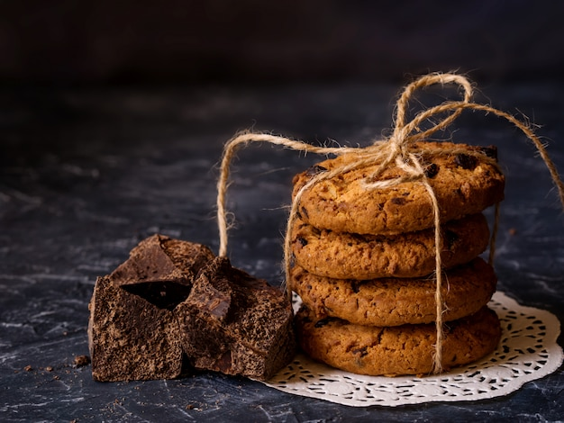 Chocolate cookies, stacked and tied with a rope, pieces of black chocolate, on a textured background.