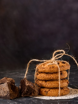 Chocolate cookies, stacked and tied with a rope, pieces of black chocolate