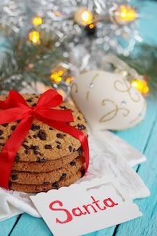 초콜릿 쿠키는 빨간 리본을 묶었습니다. 푸른 나무 테이블에 선물입니다.
