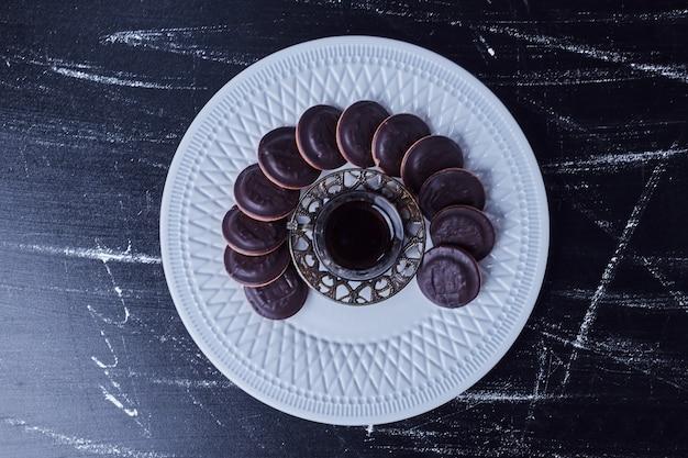 하얀 접시에 차 한 잔과 초콜릿 쿠키.