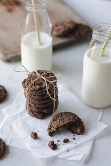 素朴な紙の上の牛乳瓶とチョコレートクッキー