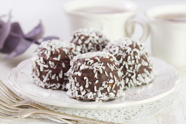 白い木製テーブルの上の白い皿にココナッツとチョコレートクッキー