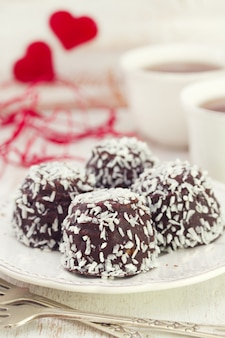 Chocolate cookies with coconut on white plate and coffee on white wooden table