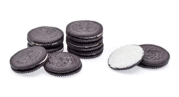 白い背景で隔離のクリームの詰め物とチョコレートクッキー。