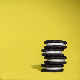 Chocolate cookies with cream stacked on a yellow background.