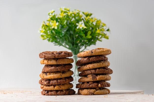 백그라운드에서 흐리게 꽃 주전자와 초콜릿 쿠키.
