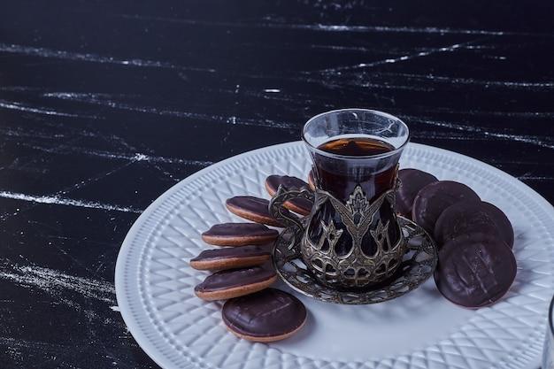 Biscotti al cioccolato con un bicchiere di tè.