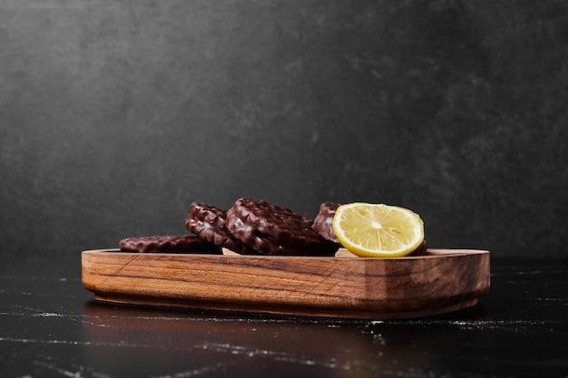 木製の大皿にレモンとチョコレートクッキー。