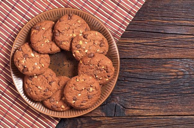 어두운 나무 배경에 접시에 견과류가 있는 초콜릿 쿠키, 위쪽