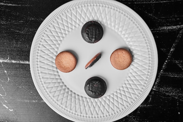 Chocolate cookies with vanilla cookies in a white plate.
