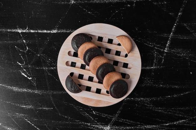 Biscotti al cioccolato con biscotti alla vaniglia su un piatto di legno.