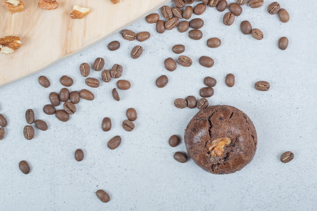 Chocolate cookies with walnuts and coffee beans on wooden board