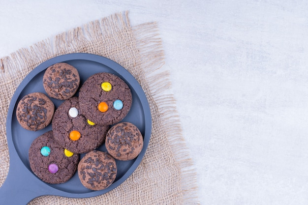 Chocolate cookies on a wooden pan on a burlap, on the marble table.