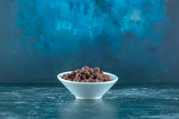 Шоколадные кукурузные шарики в миске, на синем фоне. фото высокого качества