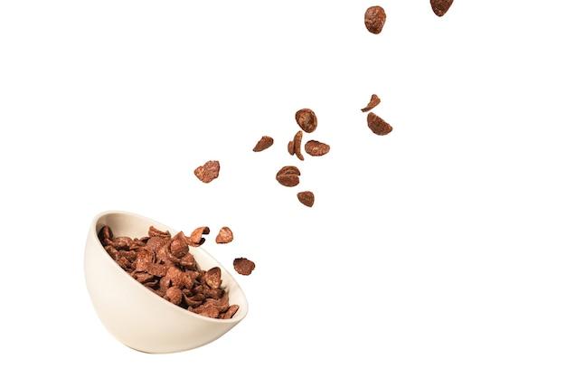 흰색 절연 흰색 그릇에 떨어지는 초콜릿 콘플레이크. 운동. 카피스페이스.
