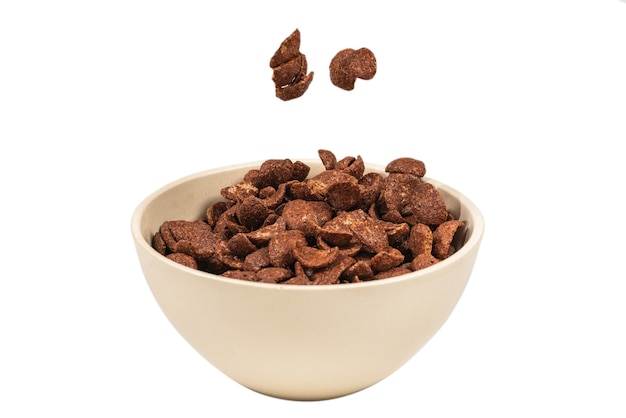 Chocolate corn flakes falling to the white bowl isolated on white. motion. copyspace.
