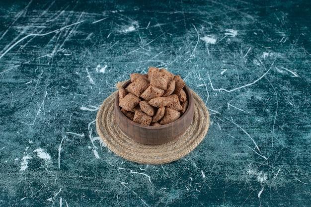 Cuscinetti di mais al cioccolato in una ciotola su un sottopentola, sulla superficie blu