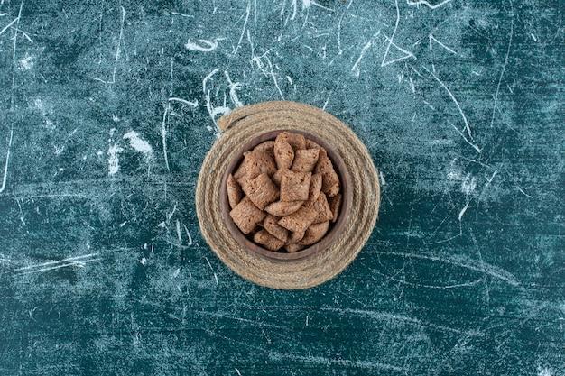 Cuscinetti di mais al cioccolato in una ciotola su un sottopentola, sul tavolo blu.