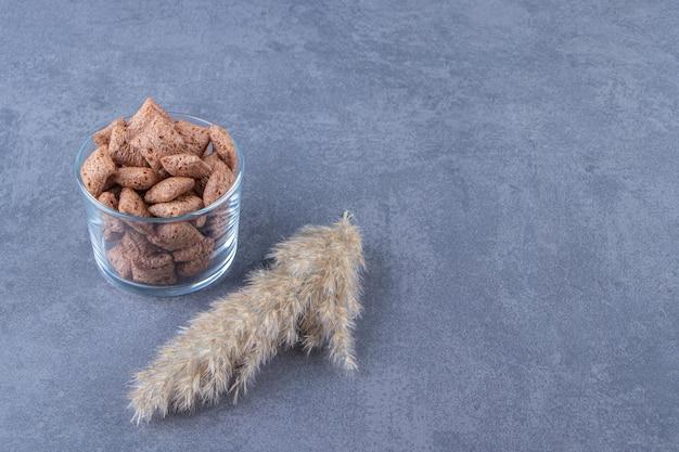 Cuscinetti di mais al cioccolato in un bicchiere accanto all'erba della pampa, sul tavolo blu.