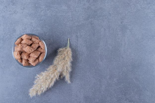 Шоколадные кукурузные подушечки в стакане рядом с пампасной травой на синем столе.