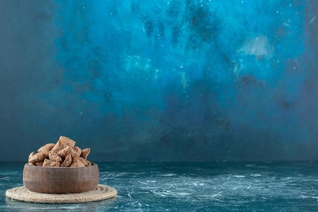 青い背景の上のtrivet 、、のボウルにチョコレートコーンパッド。高品質の写真
