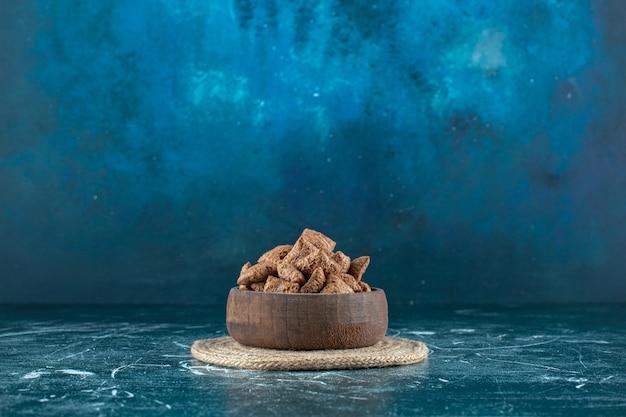 파란색 배경에 trivet에 그릇에 초콜릿 옥수수 패드. 고품질 사진