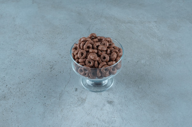 Chocolate corn ring in a glass pedestal , on the blue background. high quality photo