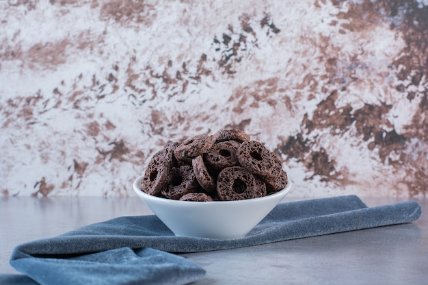 Chocolate corn rings isolated on white plate on a stone surface