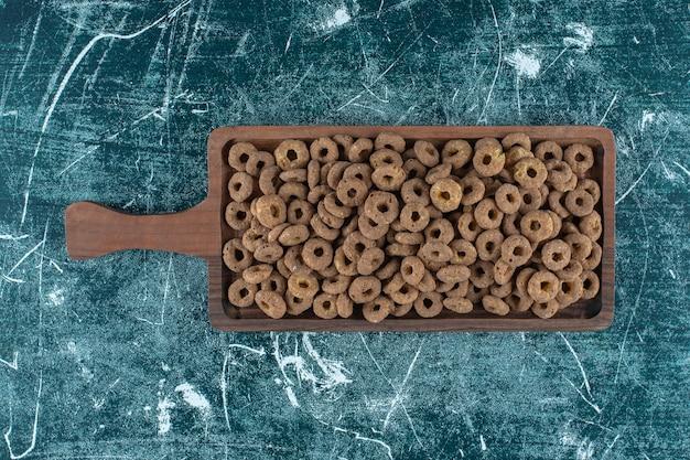 青い背景のボード上のチョコレートコーンリング。高品質の写真