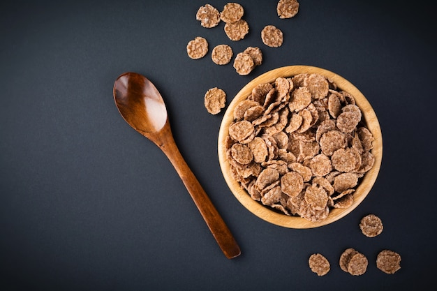 Chocolate cornflakes for breakfast in a bamboo plate on dark surface. selective focus.