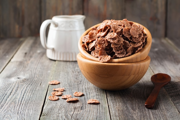 Chocolate cornflakes for breakfast in a bamboo plate on old wooden surface. selective focus.