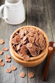 古い木の表面の竹皿で朝食用のチョコレートコーンフレーク。セレクティブフォーカス。