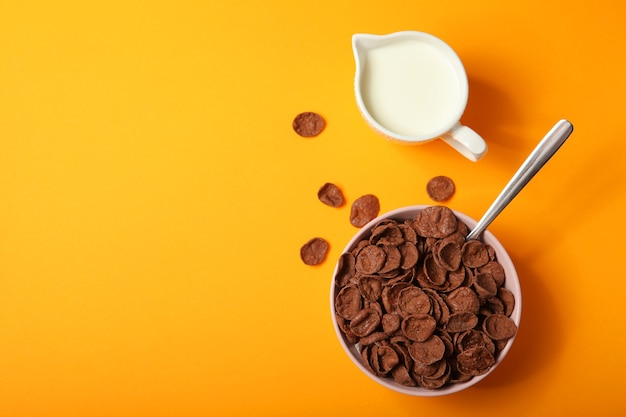 色付きの背景の朝食にチョコレートコーンフレークをクローズアップ