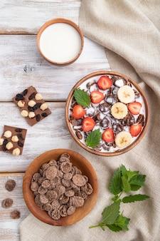 Шоколадные кукурузные хлопья с молоком и клубникой в деревянной миске на белой деревянной поверхности и льняной ткани
