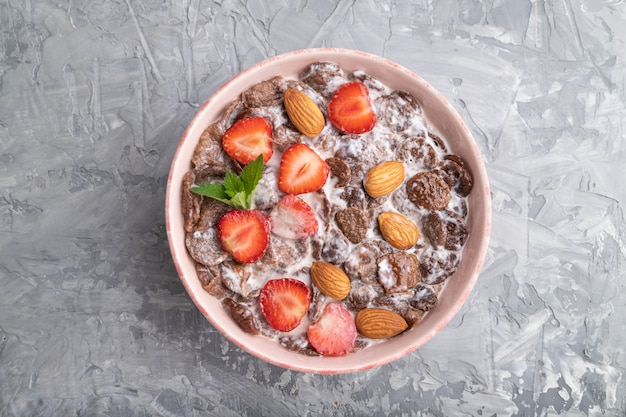 Chocolate cornflakes with milk, strawberry and almonds in ceramic bowl