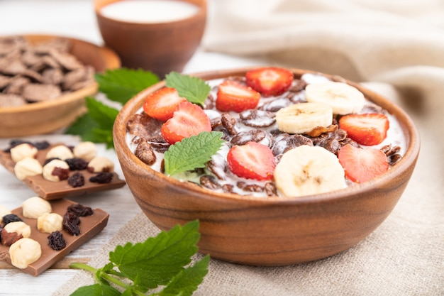 Chocolate cornflakes with milk and strawberry in wooden bowl