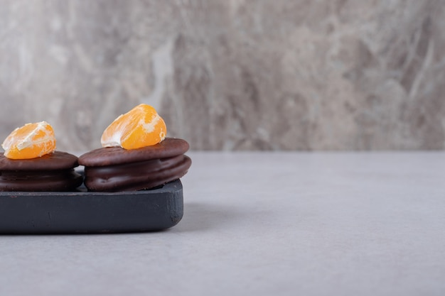 Chocolate covered cookies with tangerine slice on the wooden tray on marble table.