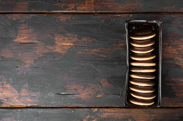 초콜릿 덮인 마시멜로 비스킷, 플라스틱 쟁반 용기, 플라스틱 쟁반 용기, 오래된 어두운 나무 테이블 배경, 위쪽 뷰 플랫 레이, 텍스트 복사 공간