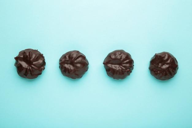 Зефир в шоколаде на синей поверхности