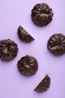 Зефир в шоколаде на фиолетовой поверхности