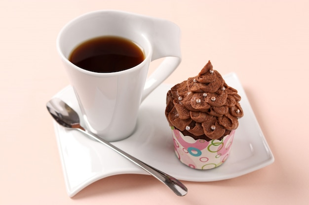 Chocolate cream cupcake and a cup of coffee arranged