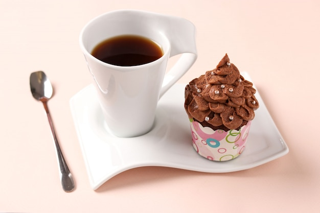 Chocolate cream cupcake and a cup of coffee