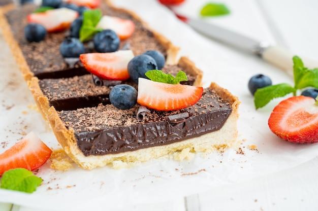 Шоколадно-кремовый пирог со свежей черникой и клубникой сверху на белом деревянном фоне