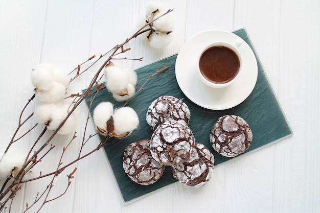 Chocolate crinkle brownie cookies in sugar powder next to cup of coffee top view