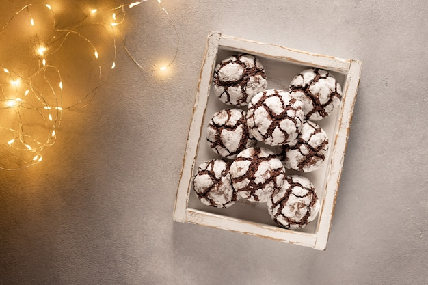 Chocolate crinkle cookies in wooden box with christmas lights festive homemade sweets