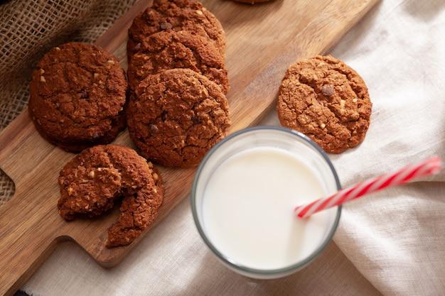 牛乳のガラスとチョコレートクリスピークッキーをクローズアップ