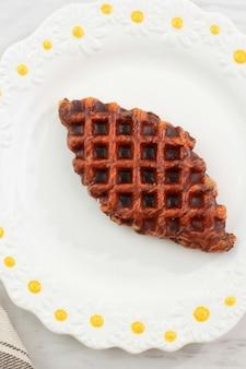 Шоколадные круассаны или круассаны в белой тарелке. croffle - это вирусный закусочный торт из южной кореи.
