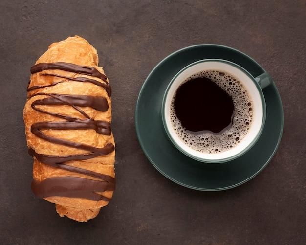 Шоколадный круассан и вид сверху кофе