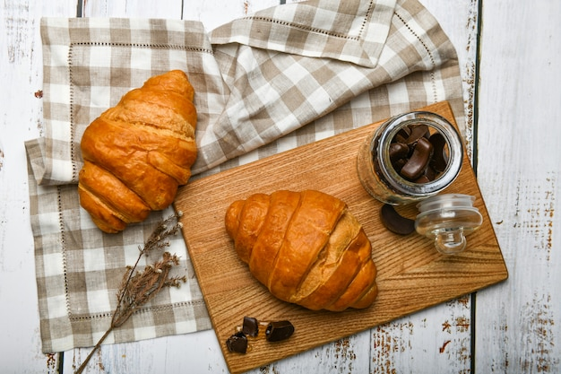 Chocolate croissants. the beginning of the morning. a cup of coffee. fresh french croissant. coffee cup and fresh baked croissants on a wooden . .