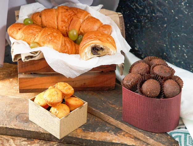 Chocolate croissants, box of pralines and muffins on a piece of wood
